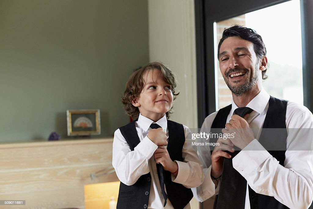 Boy adjusting tie while looking at father : Stock Photo
