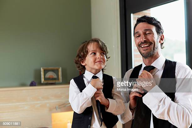 Boy adjusting tie while looking at father