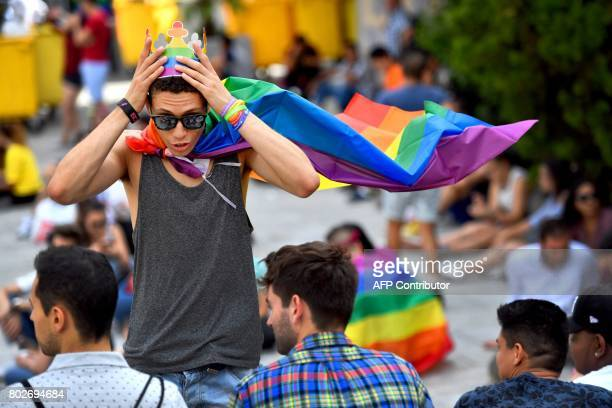 A boy adjusts a paper crown with the rainbow colours in Madrid's Chueca district on June 28 2017 before the official proclamation of the WolrdPride...