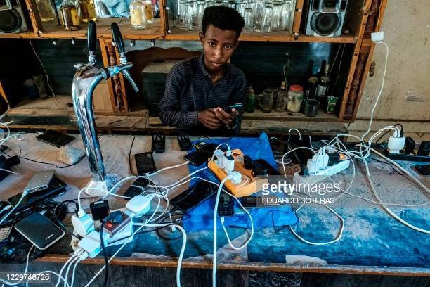 Boy administers the charge of phones at a bar in Humera, Ethiopia, on November 22, 2020. - The city has been without electricity from November 9,...