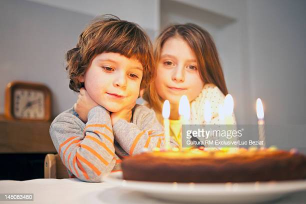 Boy admiring candles on birthday cake