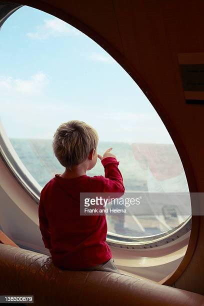 Junge Genießen Sie den Meerblick vom Schiff Fenster