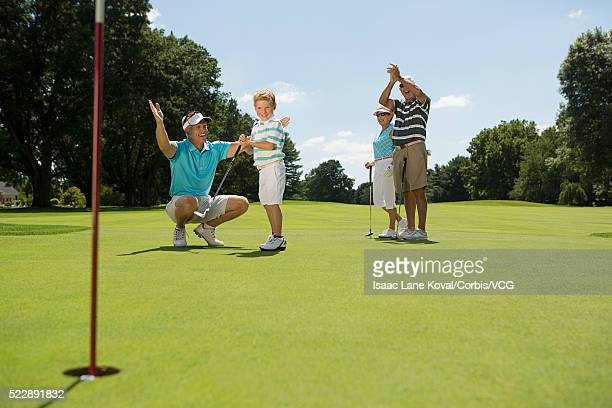 Boy (6-7) after successful shot on golf course