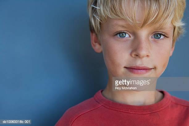 Boy (10-11 years) against blue background, portrait, studio shot, close up