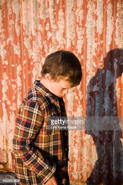 Boy against metal wall