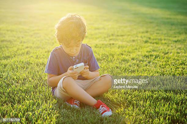 boy age 4 with cell phone - short sleeved stock pictures, royalty-free photos & images