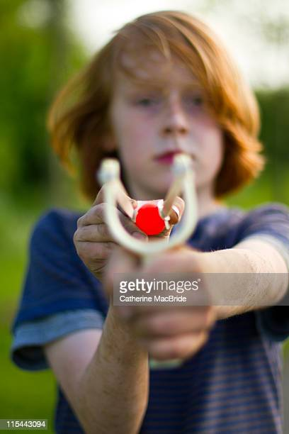 boy aiming catapult - catherine macbride stock pictures, royalty-free photos & images