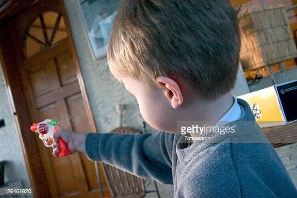Boy aiming colorful toy cap gun