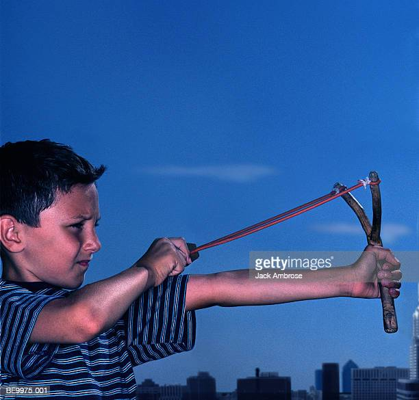 Boy (5-7) aiming sling-shot, close-up