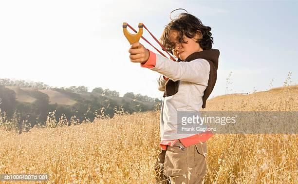 boy (8-9) aiming slingshot in field - solo un bambino maschio foto e immagini stock