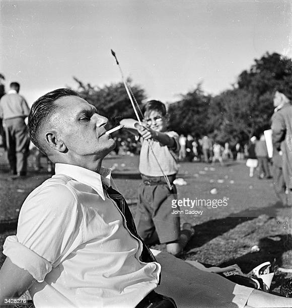A boy aims to shoot a cigarette from the mouth of a fellow spectator with a bow and arrow during the International Stoke Mandeville Games at the...