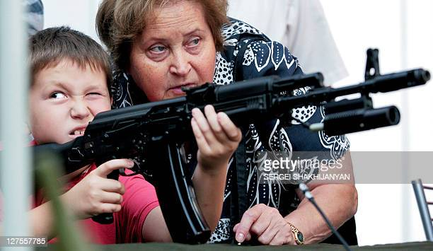 A boy aims with a fake Kalashnikov machinegun as his grandmother assists him at a weapons fair on August 23 2008 in Moscow Russian troops will patrol...