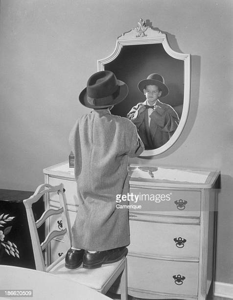 Boy all dressed up like his dad standing on a chair in front of a mirror Philadelphia PA 1958