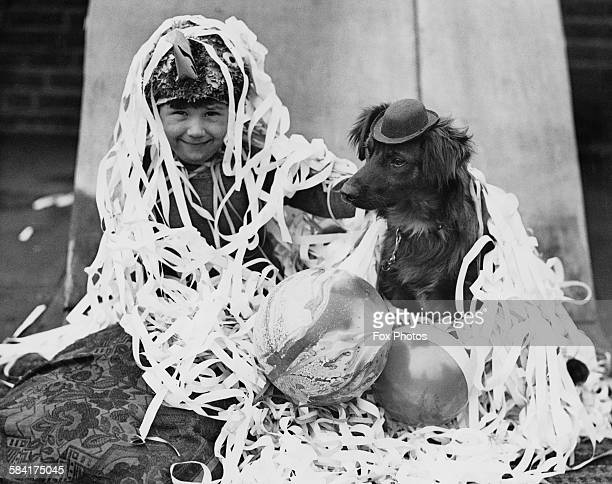 A boy and a dog at a Christmas party both covered in streamers and wearing party hats 24th December 1932