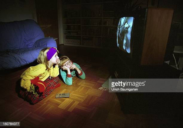 A boy and a girl are watching a horror movie on television