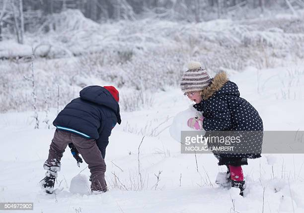 A boy and a girl build a snowman in Jalhay after a snow front reached the country on the higher part of eastern Belgium on January 14 2016 / AFP /...