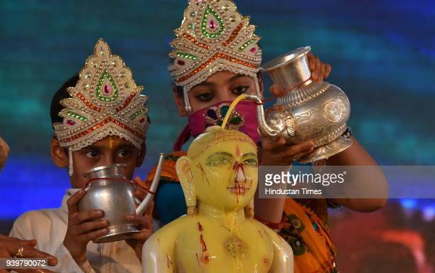 A boy and a girl dressed as Indra and Indrani perform the Maha Abhishek of Lord Mahavir with turmeric and Saffron on the occasion of Mahavir Jayanti...