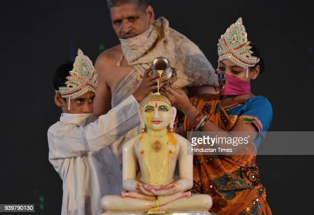 A boy and a girl dressed as Indra and Indrani perform the Maha Abhishek of Lord Mahavir with turmeric on the occasion of Mahavir Jayanti at Freedom...