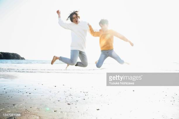 a boy and a girl jumping on the side of the wave - yusuke nishizawa stock pictures, royalty-free photos & images