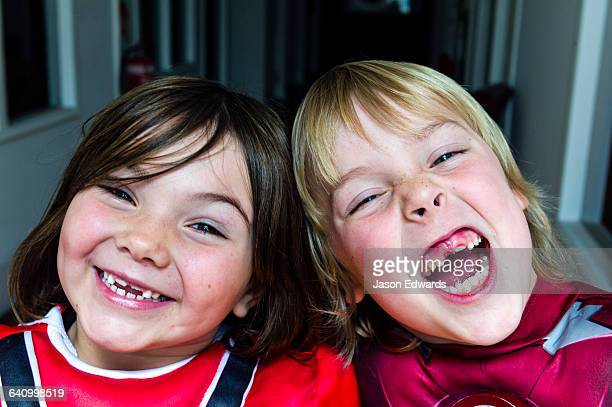 A boy and a girl laugh displaying the gaps in their front teeth.