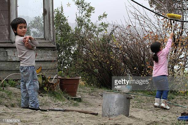 A boy and a girl play in their garden covered by ashes in Bariloche some 1600 kms south west of Buenos Aires on June 5 from Chile's Puyehue volcano...