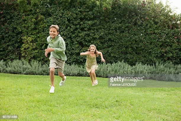 boy and a girl playing in a garden - pelouse photos et images de collection