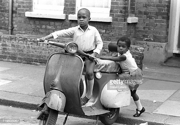 A boy and a girl playing on a motor scooter parked on an east London street circa 1970