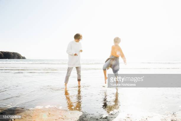 a boy and a girl playing on the water's edge - yusuke nishizawa stock pictures, royalty-free photos & images