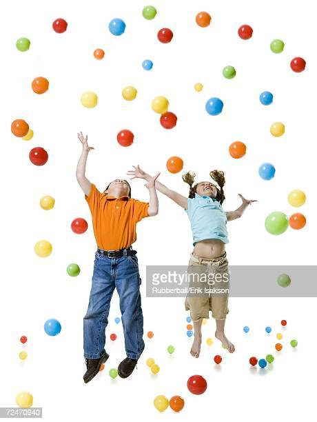 A boy and a girl playing with colored balls