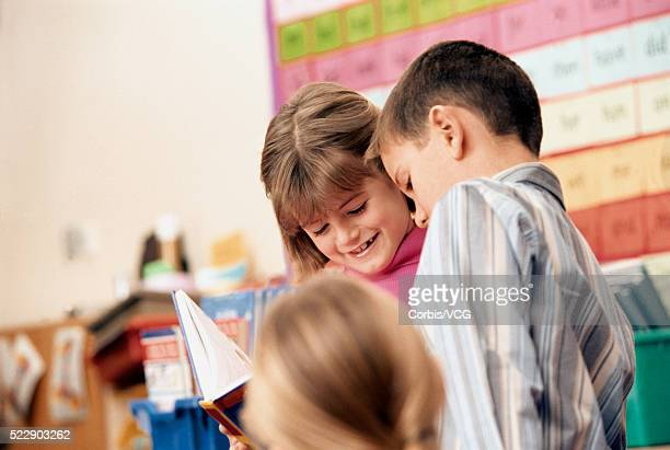 A boy and a girl reading a book together in a classroom