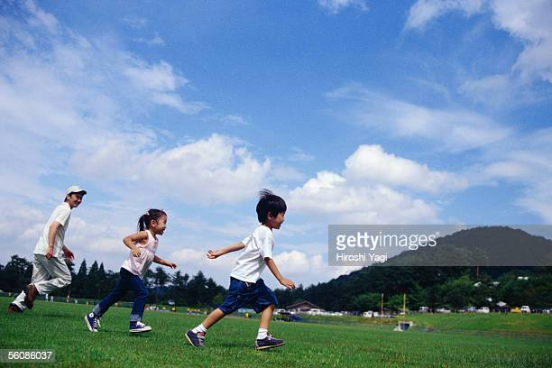 A boy and a girl running in a park