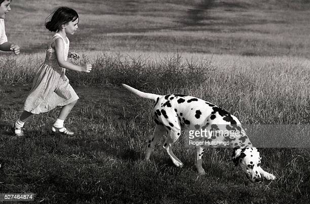 A boy and a girl running over Primrose Hill with a Dalmation Dog The dog has a smiling artful expression