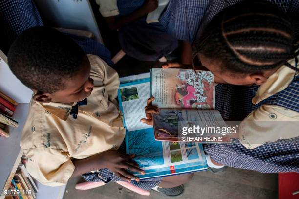 A boy and a girl sits and read books in the IRead mobile library on January 30 2018 The IRead initiative is the first mobile library service in...