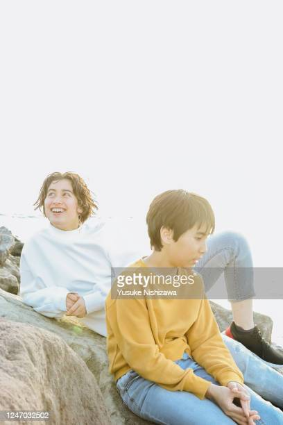 a boy and a girl sitting on a rock - yusuke nishizawa stock pictures, royalty-free photos & images