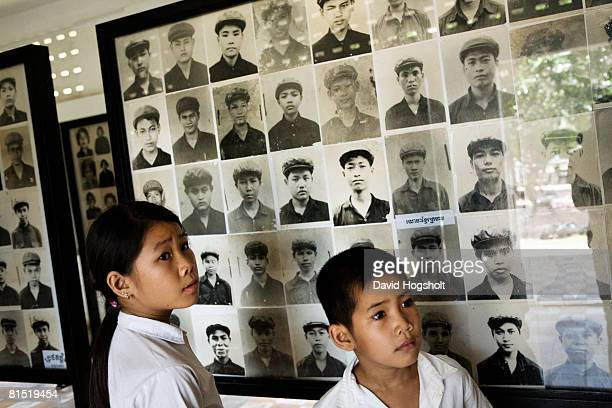 A boy and a girl stand in front of pictures of former khmer rouge cadres in the infamous S21 prison May 2 2007 in Phnom Penh Cambodia Even the cadres...