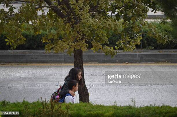 A boy and a girl walks next to a rain drenched road during a rainy autumn day in Ankara Turkey on September 26 2017 The temperature in Ankara...