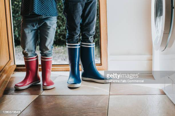 boy and a girl wearing wellies in a utility room - blue stock pictures, royalty-free photos & images