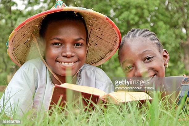 A boy and a girl with a book in the grass