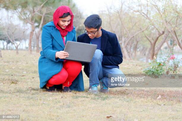 A Boy And A Girl Working On Laptop In The Garden
