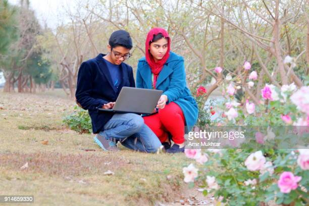 A Boy And A Girl Working On Laptop In The Park