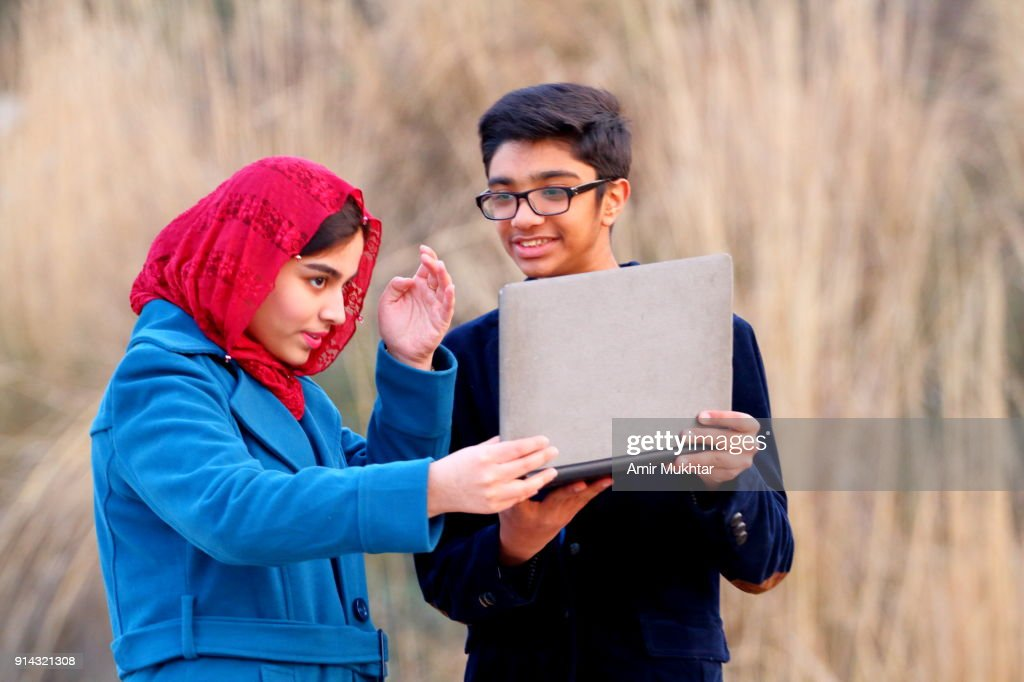 Boy And A Girl Working Outdoor On Digital Laptop : Stock Photo