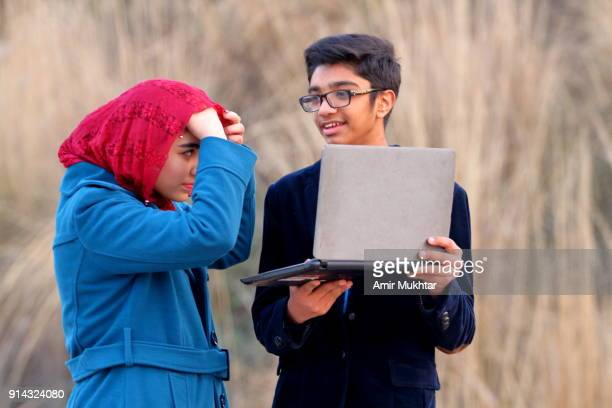 Boy And A Girl Working Outdoor On Digital Laptop