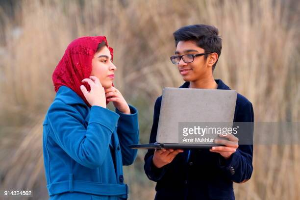 boy and a girl working outdoor on digital laptop - modest clothing stock pictures, royalty-free photos & images