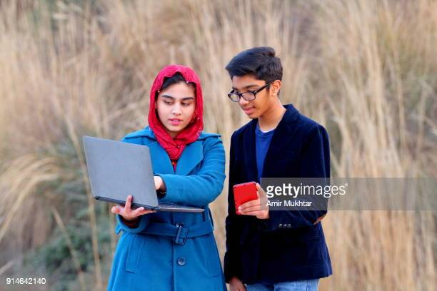 A Boy And A Girl Working Together On Laptop And Cell Phone