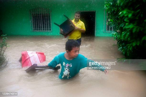 Boy and a man save chairs from a flooded house due to the heavy rains caused by Hurricane Eta, now degraded to a tropical storm, in Puerto Barrios,...