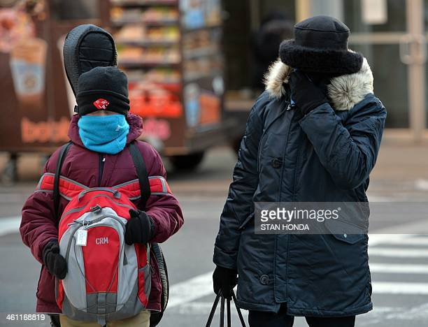 A boy and a woman bundled against the cold cross Lexington Avenue on the east side of Manhattan January 7 2014 in New York as frigid weather grips...