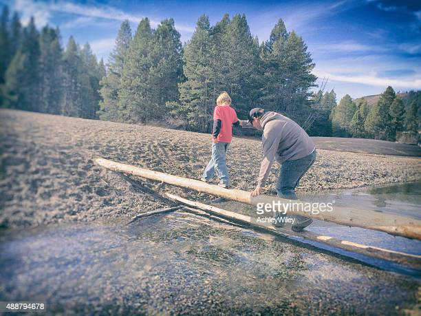 Boy and dad crossing a log together a river