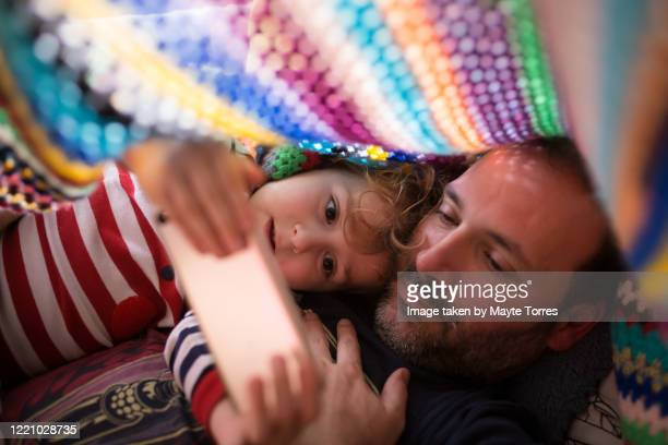 boy and dad  watching something in a smartphone under a colorful blanket - genderblend stock-fotos und bilder