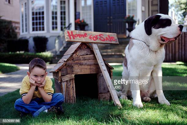 Boy and Dog by 'Home for Sale' Sign
