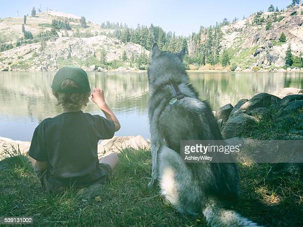 Boy and dog enjoy and afternoon on a mountain lake